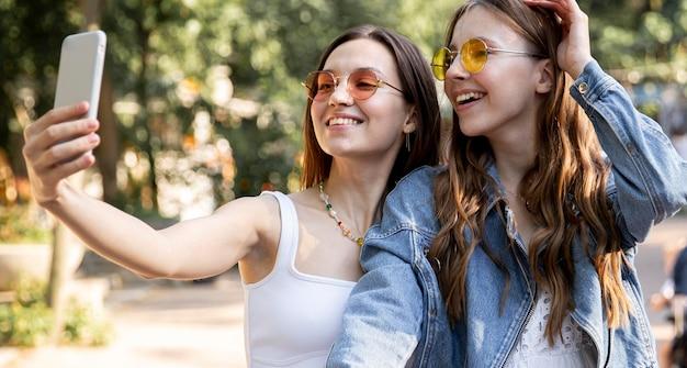 Novias montando bicicleta juntas y tomando selfie