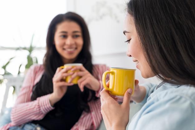 Novias multiétnicas hablando y tomando té