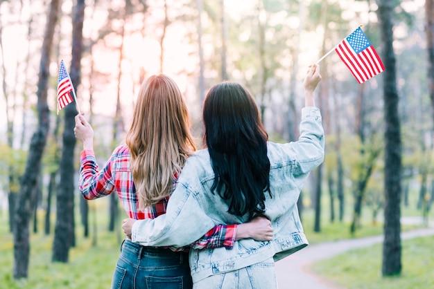 Novias con pequeñas banderas americanas abrazando al aire libre
