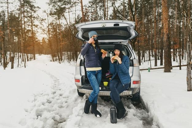 Novias ropa de invierno día nevado bosque coche hablar bebiendo café