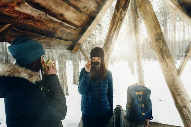 Novias ropa de invierno día de nieve bosque de invierno hablar bebiendo café