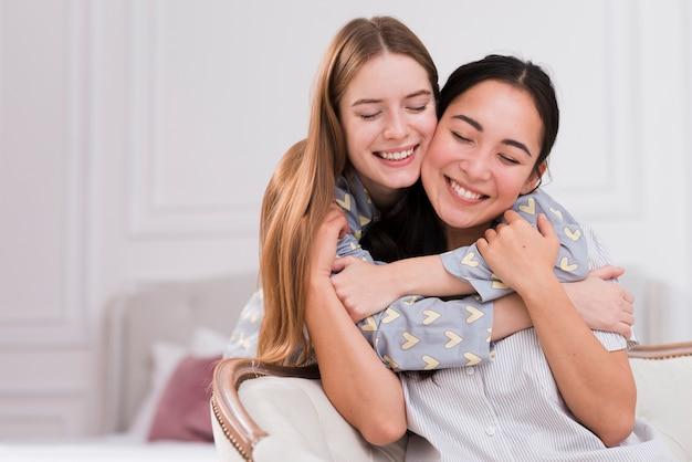 Novias sonrientes en casa abrazando