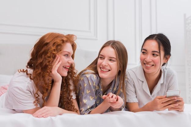 Novias sonrientes charlando en la cama