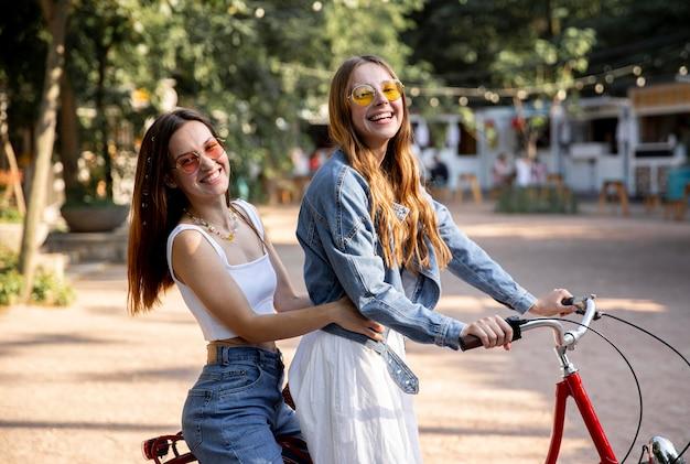 Novias sonrientes montando bicicleta juntos