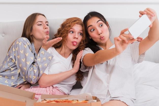 Novias tomando selfies durante la fiesta de pijama