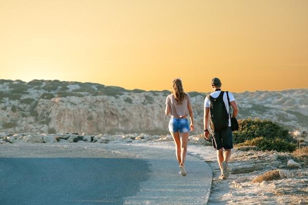 Las novias viajan por una carretera, sobre un fondo de puesta de sol y costa del mar. viajes y libertad, aventuras y direcciones para viajar.