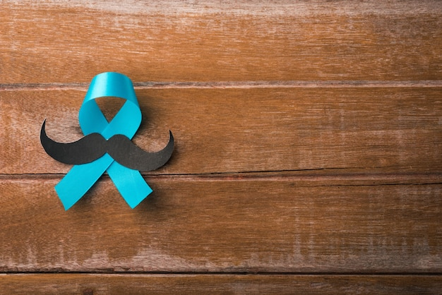 Noviembre azul, cinta azul claro con un bigote de hombre sobre fondo de madera, conciencia sobre la salud de los hombres, conciencia sobre el cáncer de próstata