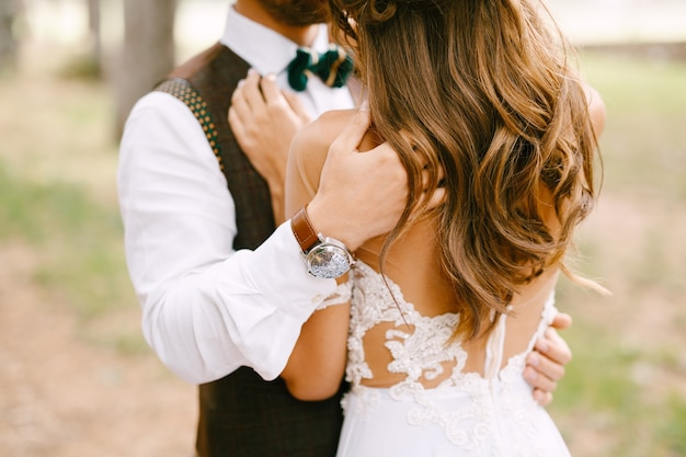 El novio abraza los hombros de la novia en un hermoso vestido blanco bordado novia