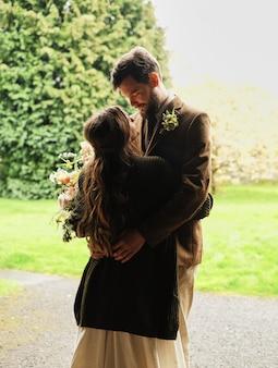 El novio abraza a la novia en un día nublado, amor, beso y ternura en los brazos.