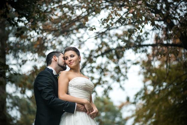 El novio abraza suavemente a la novia con un ramo desde atrás en un parque