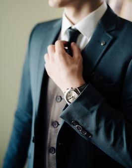 El novio se arregla la corbata alrededor del cuello antes de salir de la casa.
