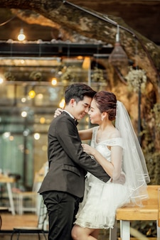 El novio asiático y la novia asiática están muy juntos y están a punto de besarse con una cara sonriente y feliz.