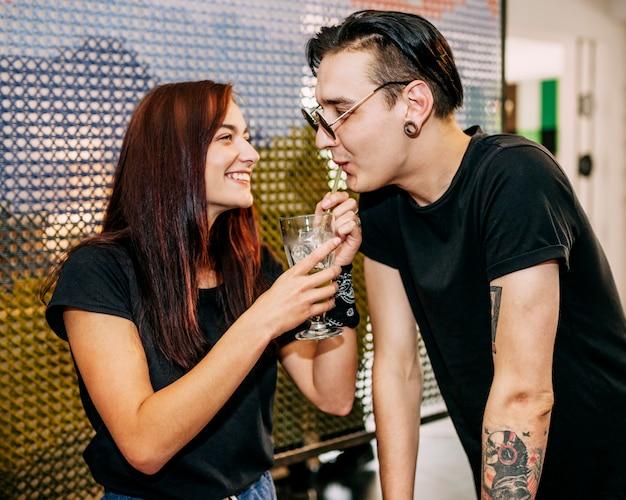 Novio bebiendo bebidas de paja con su novia