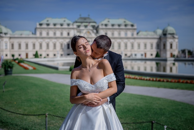 El novio besa el cuello de la novia frente al enorme palacio residencial del rey