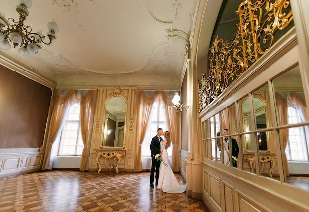 El novio besa a la novia y ella sostiene un ramo de novia. habitación con un hermoso interior con muchos espejos y grandes ventanales.