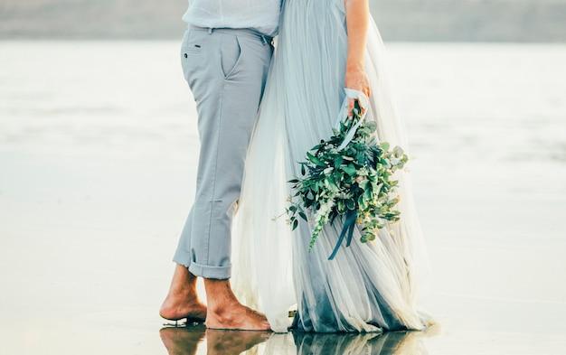 Novio de la boda de pie en el agua con bouquet abrazando