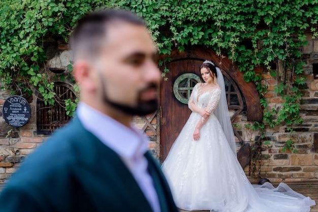 Novio borroso en primer plano y una atractiva novia caucásica en el fondo al aire libre cerca de la puerta de madera cubierta de hiedra