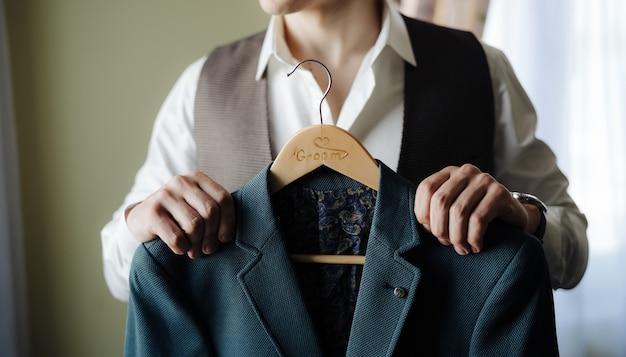El novio con una camisa blanca y un chaleco sostiene una chaqueta en una percha