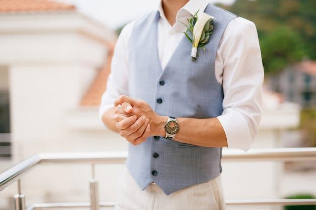 El novio con una camisa y un chaleco con un boutonniere se encuentra en el balcón en la mañana antes de la