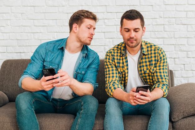Novio celoso espiando a su amigo hombre mirando su teléfono