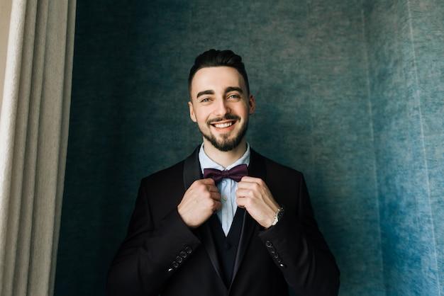 Novio elegante en camisa blanca y corbata de moño posando a la luz de la ventana. retrato seguro y feliz del hombre. novio preparándose en la mañana. foto de boda creativa