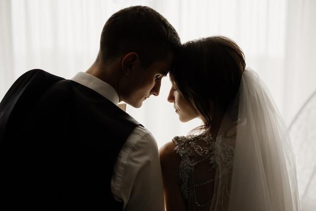 El novio elegante y la novia hermosa están parados frente a la ventana con las cabezas inclinadas el uno al otro. boda, amor, concepto de relación. clave baja. retrato de cuerpo entero.