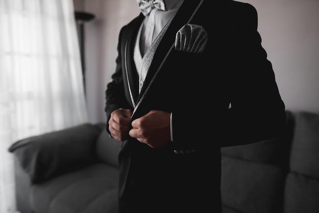Novio en esmoquin negro y pajarita gris que se pone correctamente los botones de su chaqueta