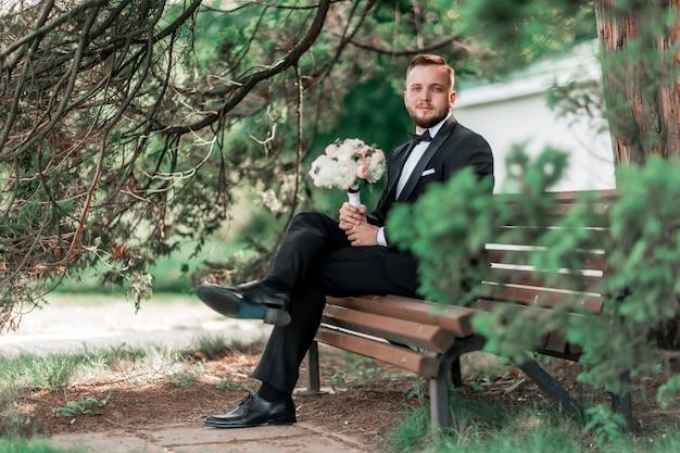 El novio está esperando a la novia sentada sentada en el banco
