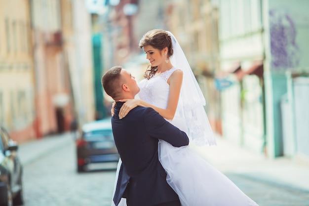 Novio gentil novia inclinada, sosteniéndola en sus brazos y besos apasionados, foto de la boda en un día soleado sobre un fondo de paredes de color arena. pareja de recién casados bailando en el parque, calle tango.