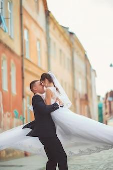 Novio gentil novia inclinada, sosteniéndola en sus brazos y besos apasionados, foto de la boda en un día soleado sobre un fondo de paredes de color arena.