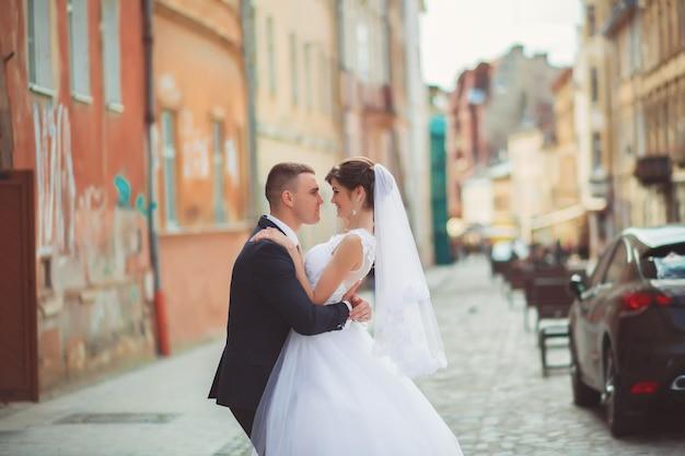 Novio gentil novia inclinada, sosteniéndola en sus brazos y besos apasionados, foto de boda en un día soleado