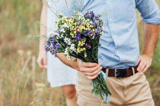 Novio con hermoso ramo de flores silvestres