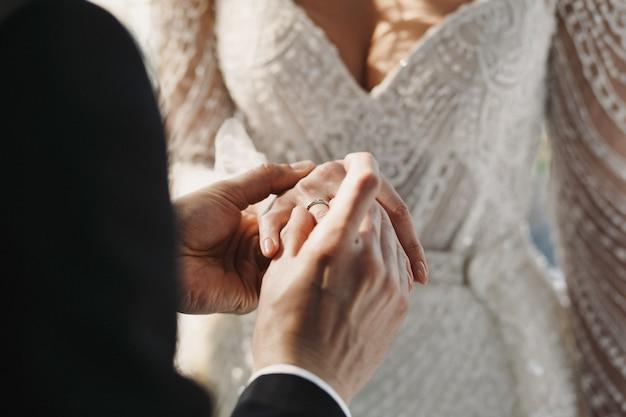 El novio lleva un anillo de bodas en el dedo de la novia