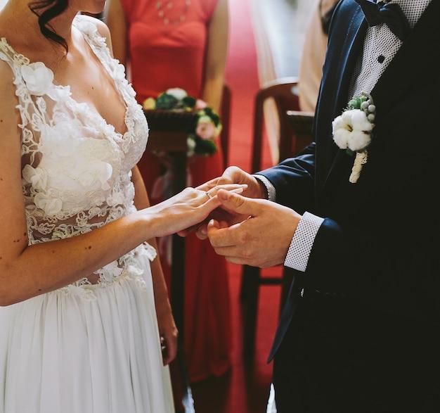 El novio lleva el anillo en el dedo de la novia en la iglesia