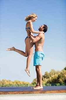 Novio llevando a su novia junto a la piscina