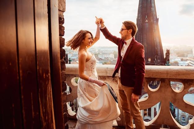 Novio en un lujoso traje bailando con su amada en el balcón.