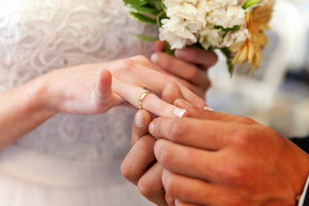 Novio mano poniendo el anillo de bodas en dedo novia