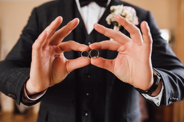 Novio muestra dos anillos de boda, sin rostro.