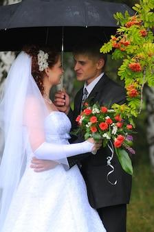 Novio y novia, besándose bajo la lluvia