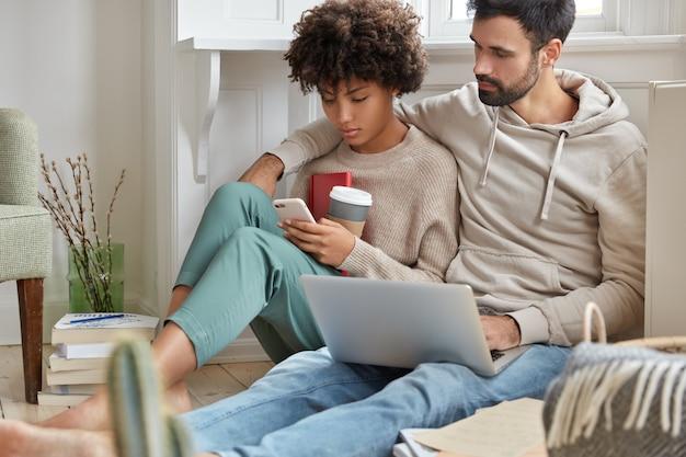 El novio y la novia descansan después de estudiar, ven fotos en las redes sociales, usan tecnologías modernas para el entretenimiento, siéntate en el piso en un apartamento moderno y disfruta de una bebida fresca en un vaso de papel desechable.