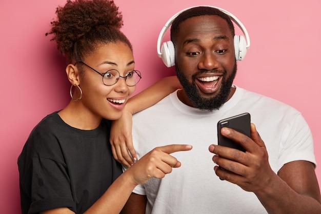El novio de la novia étnica feliz mira alegremente el dispositivo del teléfono inteligente, señala la pantalla, mira videos divertidos, navega por las redes sociales, escucha música en auriculares, pasa el tiempo libre usando la tecnología moderna