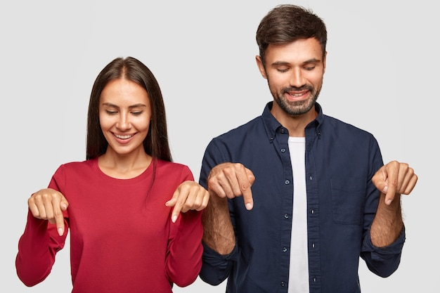 Novio y novia joven positiva con expresión alegre, notar algo agradable hacia abajo, señalar con ambos dedos índices