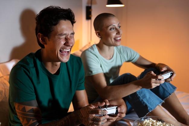 Novio y novia jugando videojuegos juntos en casa