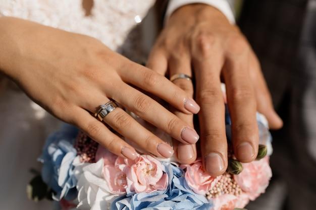 Novio y novia ponen sus manos sobre las flores