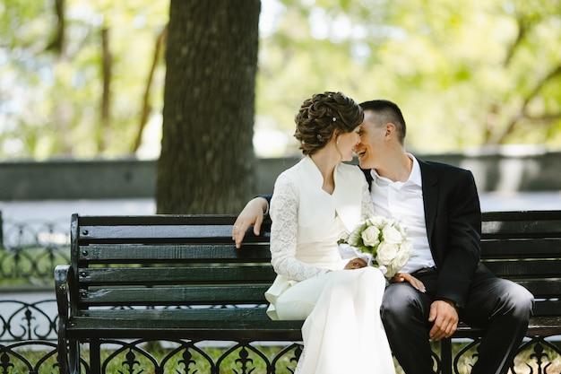 Novio con novia sentarse en un banco y sonreír