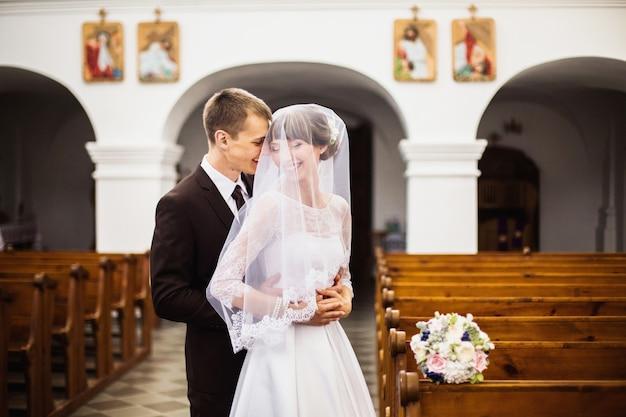 Novio y novia con un vestido blanco en la iglesia. ceremonia de la boda. familia feliz