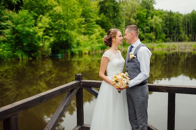 Novio y la novia en vestido de novia gainst una terraza de madera en el lago.