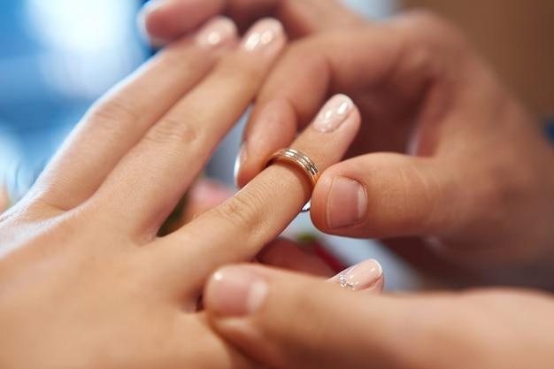 El novio pone el anillo en el dedo de la novia en la boda