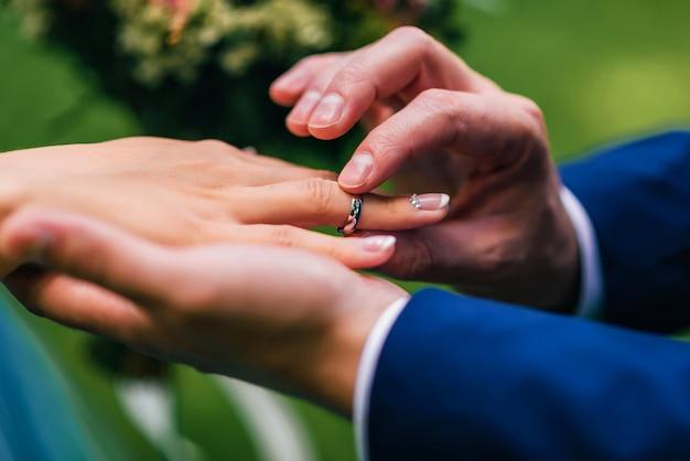 Novio pone a la novia un anillo de bodas de oro blanco en su dedo
