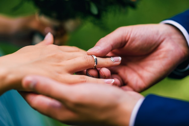 Novio le pone a la novia un anillo de bodas de oro en su dedo